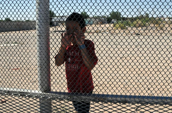 Nine-year-old Luis standing on the Mexican side of the fence at Anapra and talking with me and a friend. (Photo by Heath Haussamen)