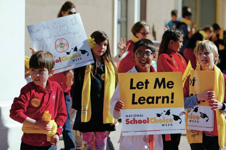 Jack Bensch, 9, a fourth-grader at the New Mexico International School, holds a sign outside the state Capitol during a rally Thursday for National School Choice Week.