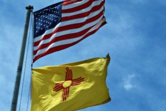 The flags of the United States and, below it, New Mexico.